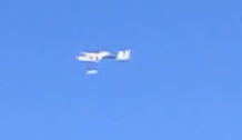 A still from the video (slightly out of focus), showing the bottle being released from the plane.